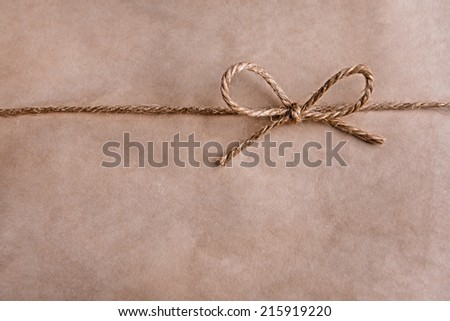 Paper texture with rope bow, close-up - stock photo