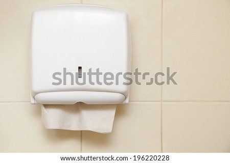 Paper towel dispenser on the wall in the bathroom - stock photo