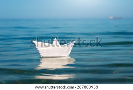 Paper toy ship and deep blue sea. Conceptual design. - stock photo