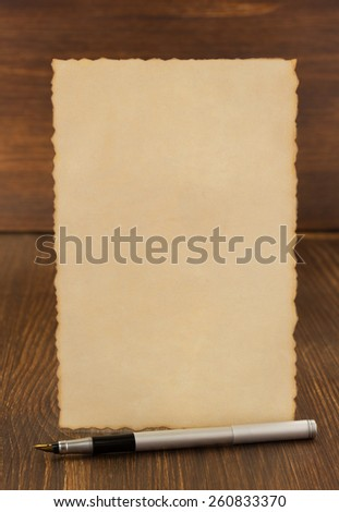 paper vintage parchment on wooden background - stock photo