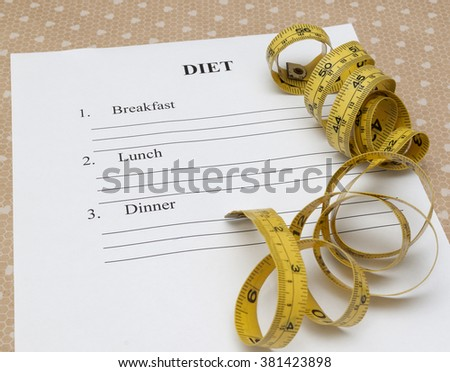 paper with diet plan and roll yellow measure tape on yable - stock photo