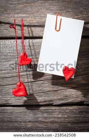 paper with hearts on a wooden background  - stock photo