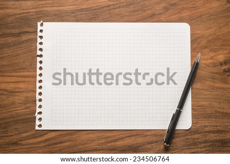 Paper with pen on a wooden desk   - stock photo