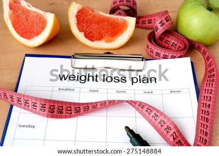 Paper with weight loss plan and grapefruit - stock photo