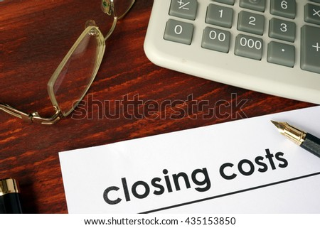 Paper with words closing costs on a wooden background.