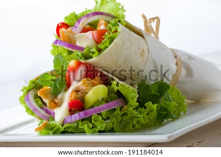 Paper wrapped chicken and salad tortillas drizzled with mayonnaise served on a tray for healthy Tex-mex cuisine - stock photo