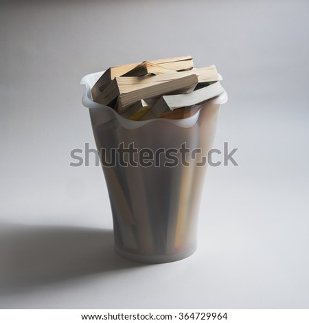 paperback books in waste basket - stock photo