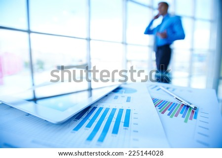 Papers, digital tablet and pen on background of businessman by office window - stock photo