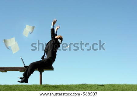 Papers float through the air, as a young businessman throws his hands in the air in joy - stock photo