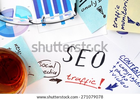 Papers with text, graphs and seo (search engine optimization). - stock photo