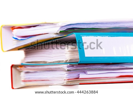 Paperwork. Stack of file folders, ring binders on office desk.