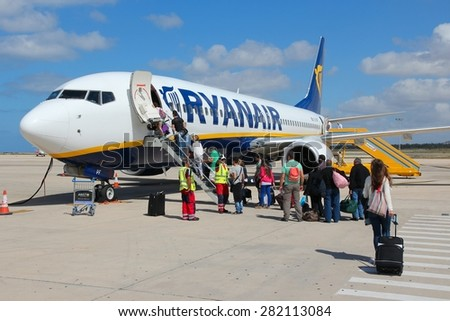 PAPHOS, CYPRUS - MAY 18, 2014: Passengers board Ryanair Boeing 737-800 aircraft in Paphos. Ryanair had 866.7 million EUR of net income in financial year ending March 2015. - stock photo