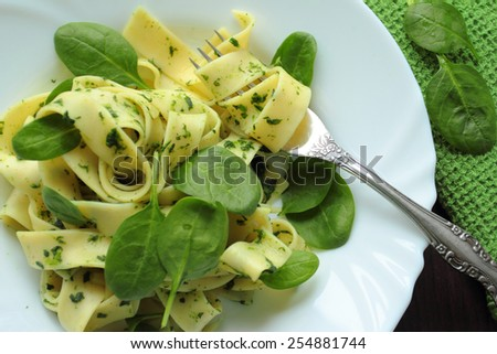 Pappardelle pasta with fresh spinach on white plate - stock photo