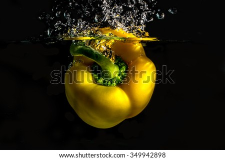 Paprika falling into the water with a splash of water and air bubbles, on a black background - stock photo