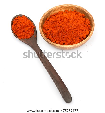 Paprika powder in wooden bowl and wooden spoon over white background