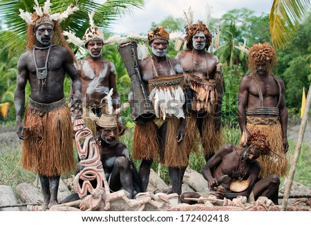 PAPUA (IRIAN JAYA), ASMAT , INDONESIA : JANUARY 18: Asmats headhunters and woodcarver in traditional and national tribal customs, dresses  on January 18, 2009 in Papua (Irian Jaya), Indonesia.  - stock photo
