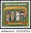 PAPUA NEW GUINEA - CIRCA 1973: A stamp printed in Papua New Guinea shows masks, circa 1973. - stock photo