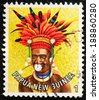 PAPUA NEW GUINEA - CIRCA 1978: A used postage stamp from Papua New Guinea illustratinga man in native head dress, issued in 1978. - stock photo