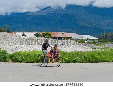 PAPUA PROVINCE, INDONESIA - DEC 27: A trishaw driver on the street   in Wamena, at island New Guinea, Indonesia on Dec 27, 2010. - stock photo
