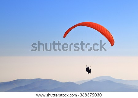 Para glider flying high above Bucegi mountains, Romania - stock photo