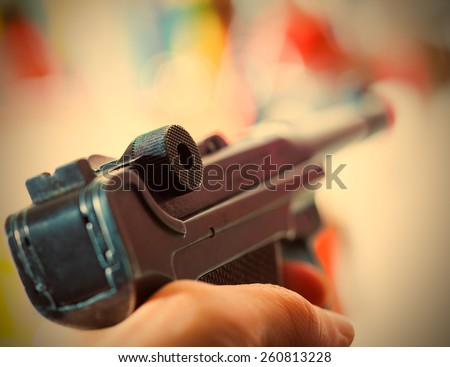 Parabellum automatic pistol in a hand, shallow depth of field. close-up. instagram image retro style - stock photo