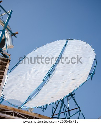 Parabolic reflectors at a rooftop solar thermal plant being used to generate heat for cooking at an Industrial Kitchen in Ahmedabad, India - stock photo