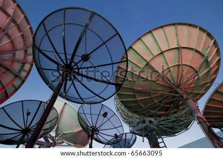 Parabolic satellite dish space technology receiver over blue sky - stock photo