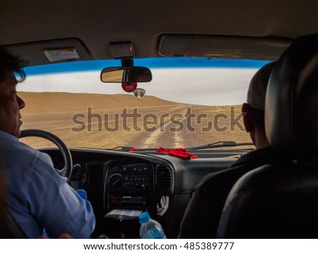 PARACAS RESERVE, PERU - AUGUST 2016 : Two men driving through a road