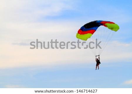 Parachute descending under the clouds