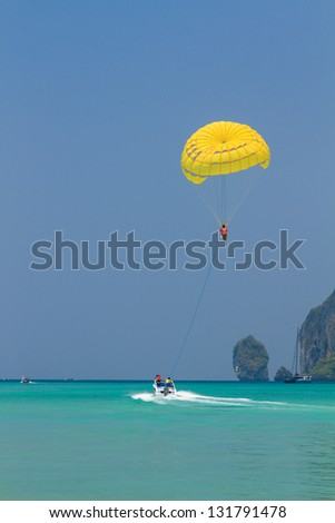 Parachute surfer being hauled by a motorboat in Thailand - stock photo
