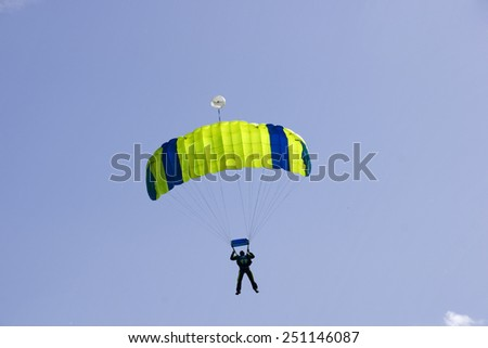 Parachutist jumping on a background of blue sky