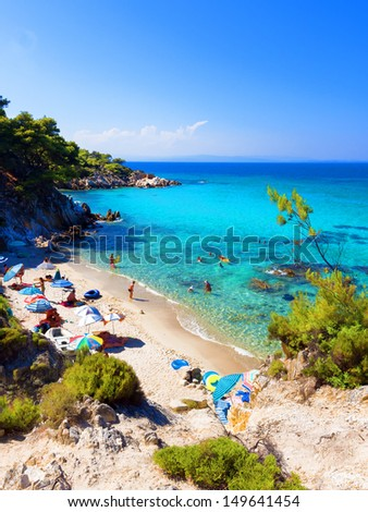 Paradise bay beach with rocks in water with cloud sky, Halkidiki, Greece  - stock photo