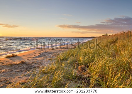 Paradise Beach. Beautiful remote coastline with sand dunes and dune grass in the foreground. - stock photo