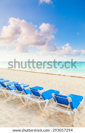 Paradise beach resort with palms and white sand, focus not on chairs - stock photo
