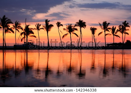 Paradise beach sunset or sunrise with tropical palm trees. Summer travel holidays vacation getaway colorful concept photo from sea ocean water at Big Island, Hawaii, USA. - stock photo