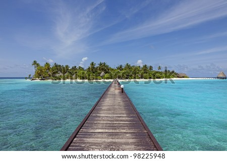 paradise island - jetty over blue ocean leading to a beautiful maldivian island with gorgeous beach and lots of palm trees - stock photo
