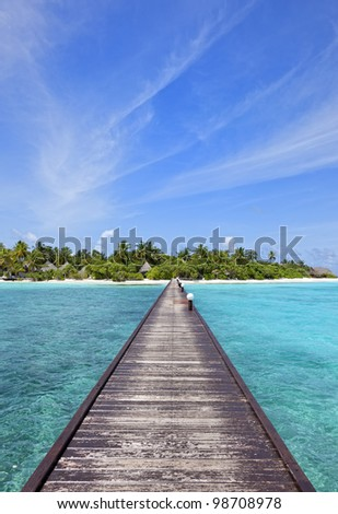 paradise island  jetty over blue ocean leading to a beautiful maldivian island with gorgeous beach and lots of palm trees vertical shot - stock photo