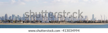 Paradise Island with modern villas with Marina High luxury blue skyscrapers in the background. Dubai, United Arab Emirates 2016. - stock photo