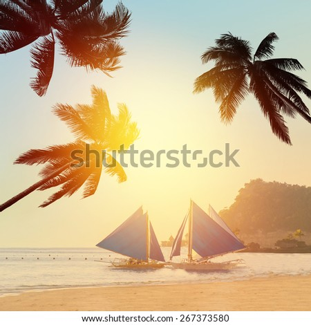 Paradise tropical beach at sunset (sunrise) with coconut palm trees and sailboats - stock photo