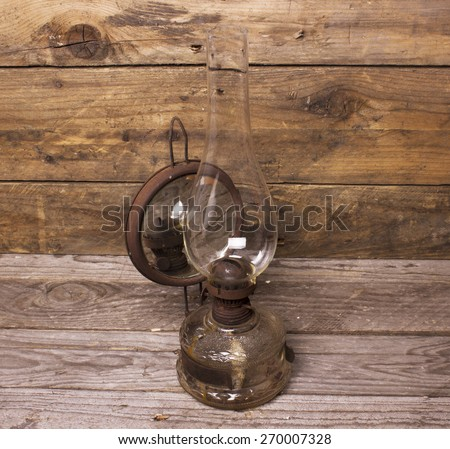 paraffin lamp on wooden wall - stock photo