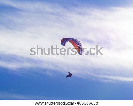 Paraglide paragliding silhouette shadow flyer. Paraglider jump and fly over mountains and clouds in winter day   - stock photo