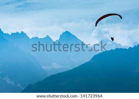 Paraglide shadow figure over Alps peaks - stock photo