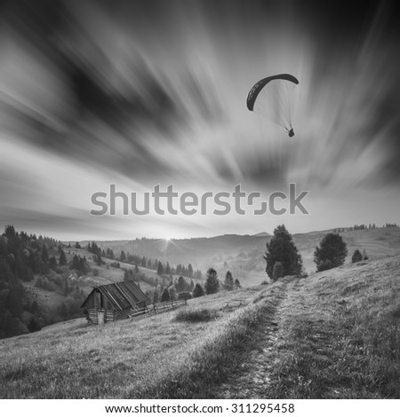 Paraglide silhouette flying over Carpathian misty mountains against beautiful sky. Monochrome picture - stock photo