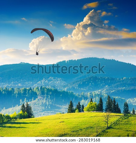 Paraglide silhouette flying over Carpathian misty mountains in a light of sunset. - stock photo