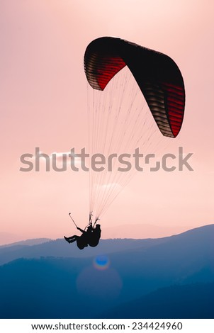 Paraglide silhouette flying over Carpathian peaks and clouds  - stock photo
