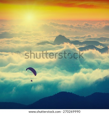 Paraglide silhouette over mountain peaks. Sunrise in a high mountains foggy valley of Crimea, Ukraine - stock photo