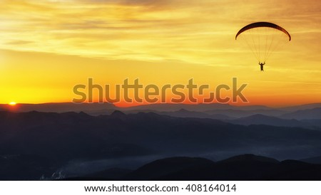 Paraglide silhouette over mountains at the sunset - stock photo