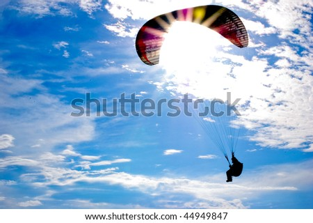 Paraglider against sun on blue sky
