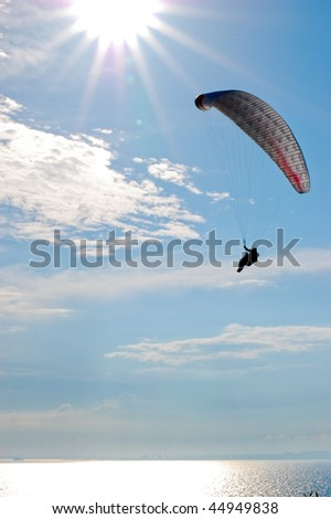 Paraglider against sun on blue sky vertical - stock photo