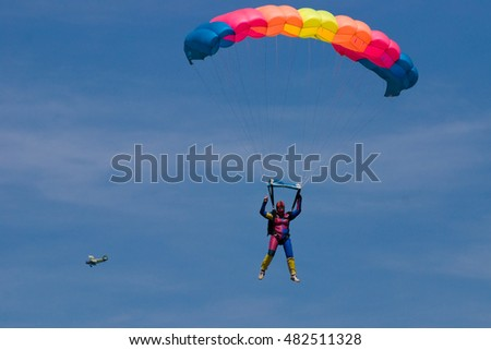 Paraglider falling against a blue sky with an airplane in the background.